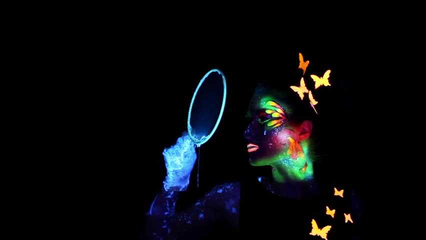 Video of young  woman with luminous make up blowing bubbles in darkness - HD stock footage clip