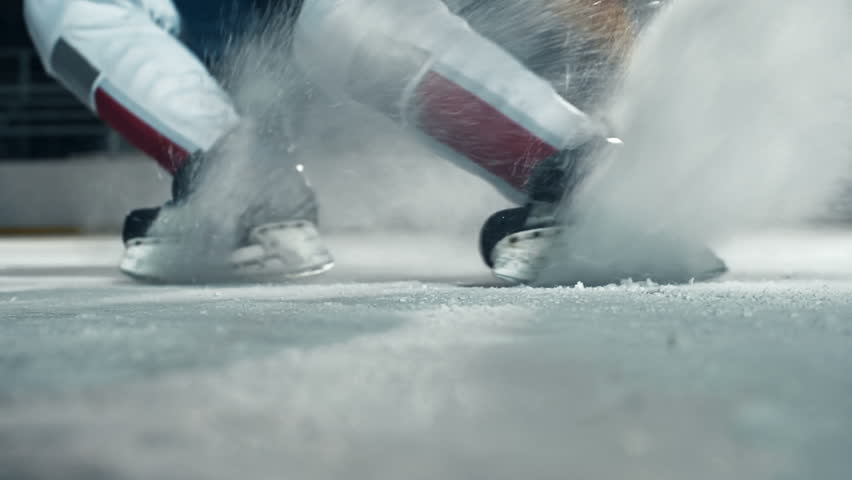 Low angle of hockey player running towards camera on skates and doing a turn cutting ice to powder