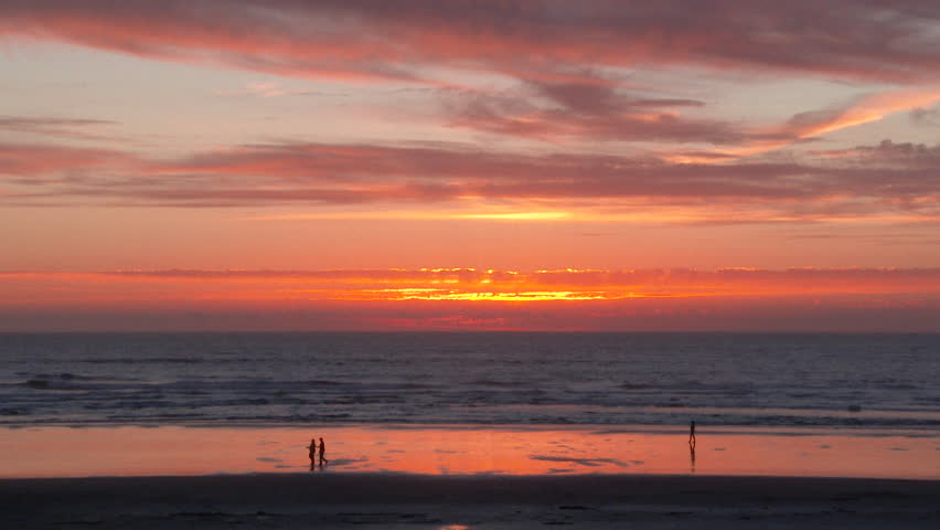 Silhouetted people walking on sandy shores of the Oregon Coast at sunset.