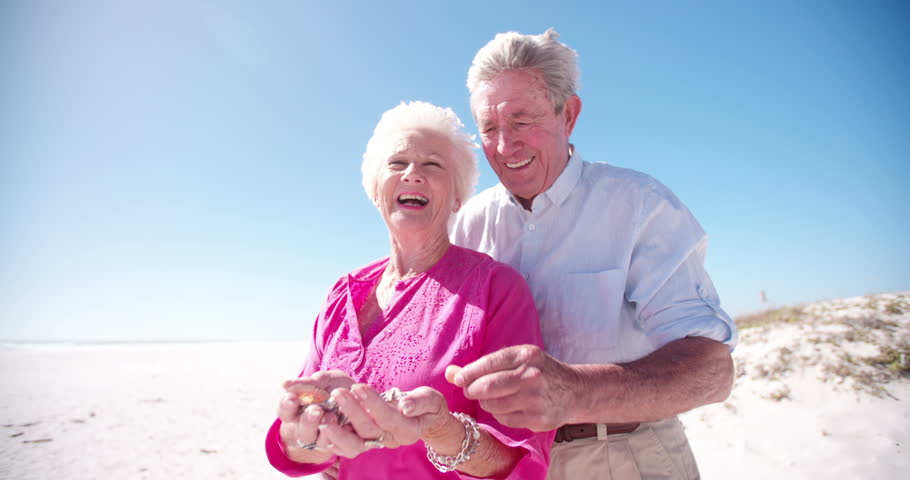 Elderly couple with collection of shells from the beach