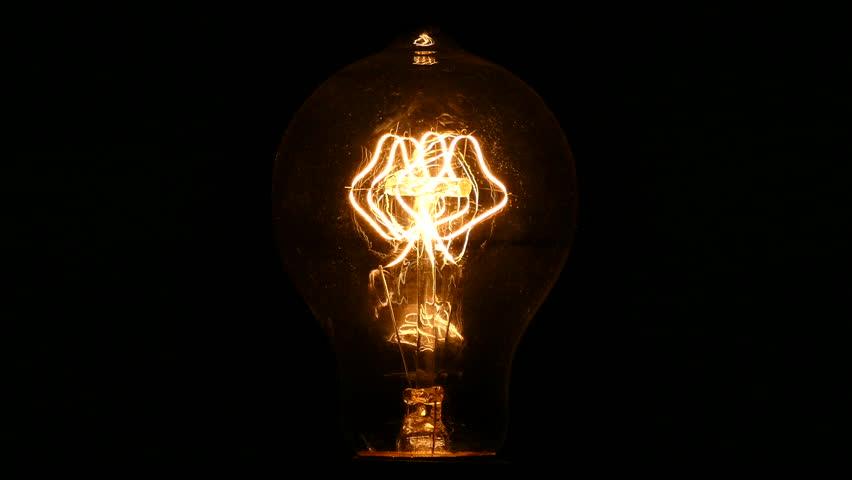 Close up of glowing vintage incandescent light bulb filament