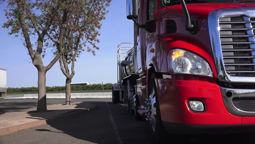 Big red tanker semi truck parked at a rest stop starts to drive away. - 4K stock footage clip