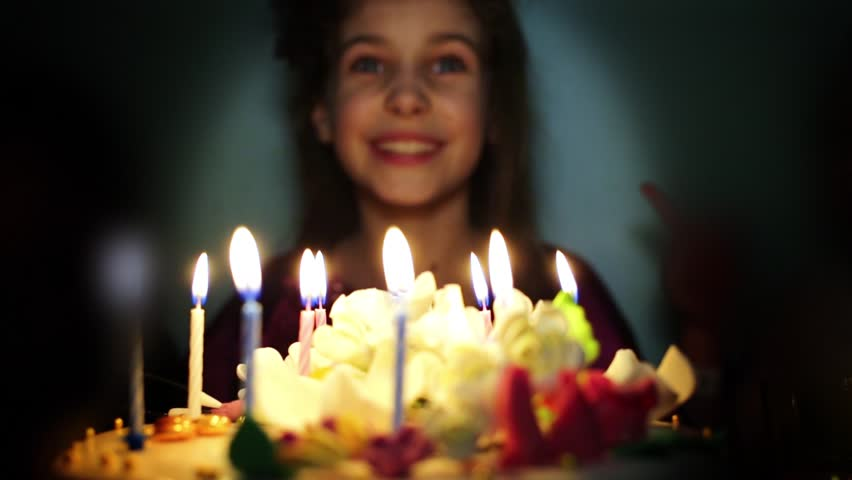 Smiling little girl blows out candles on birthday cake.