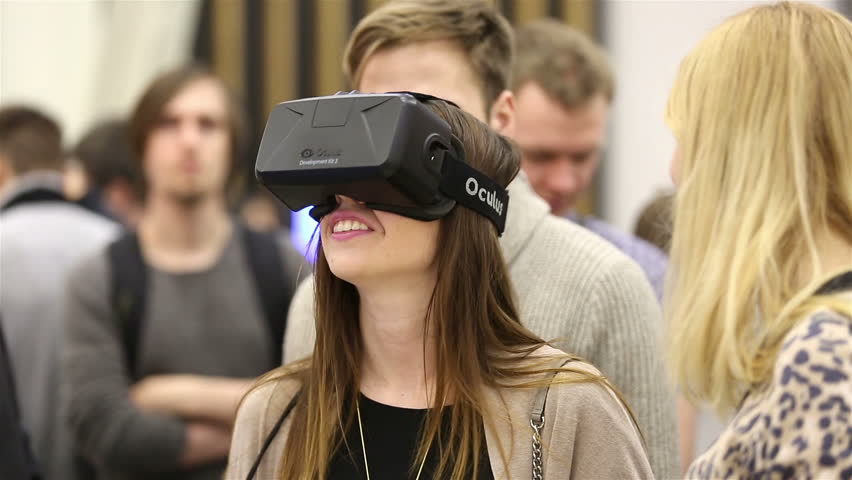 MOSCOW, RUSSIA - MARCH 29, 2015: Virtual reality game. Girl uses head mounted display Oculus Rift. Exhibition of modern technologies TechTrends Expo. - HD stock footage clip