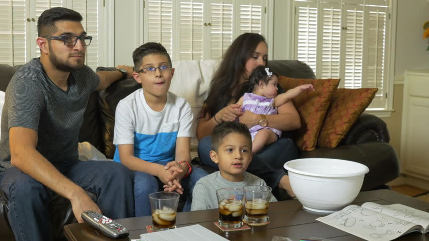 A lovely Hispanic family with two cute boys enjoying popcorn as they all sit together to watch TV. - 4K stock footage clip