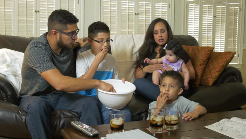 An attractive Hispanic family sitting together enjoying popcorn and television show. - 4K stock footage clip