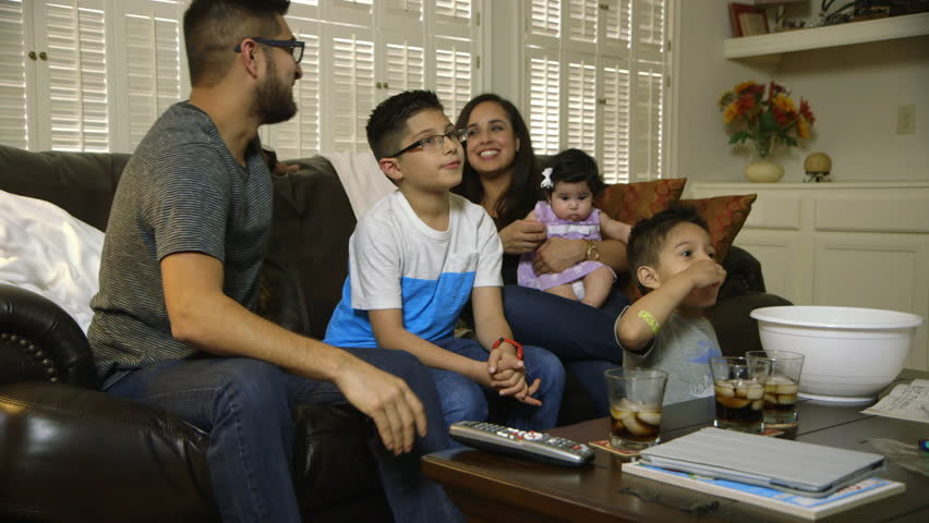 An attractive Hispanic family with two cute boys enjoying popcorn as they all watch TV together. - HD stock video clip