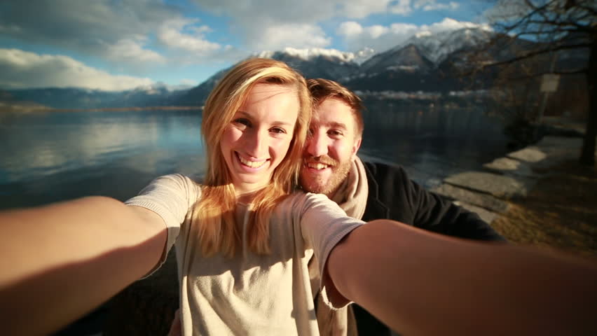 Cheerful young couple by the lake taking a selfie, man kissing woman on the cheek. Sunset light on their faces, lake and mountain landscape as the background.