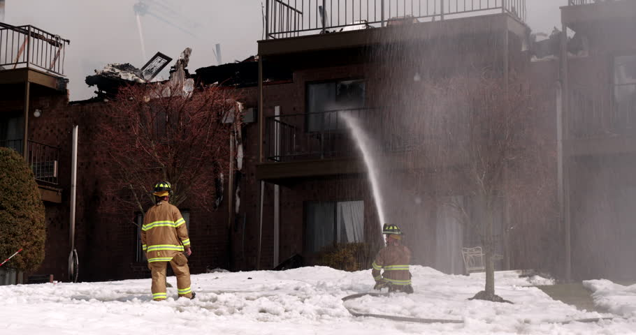 Two firemen spraying water on apartment building fire in winter - 4K stock footage clip