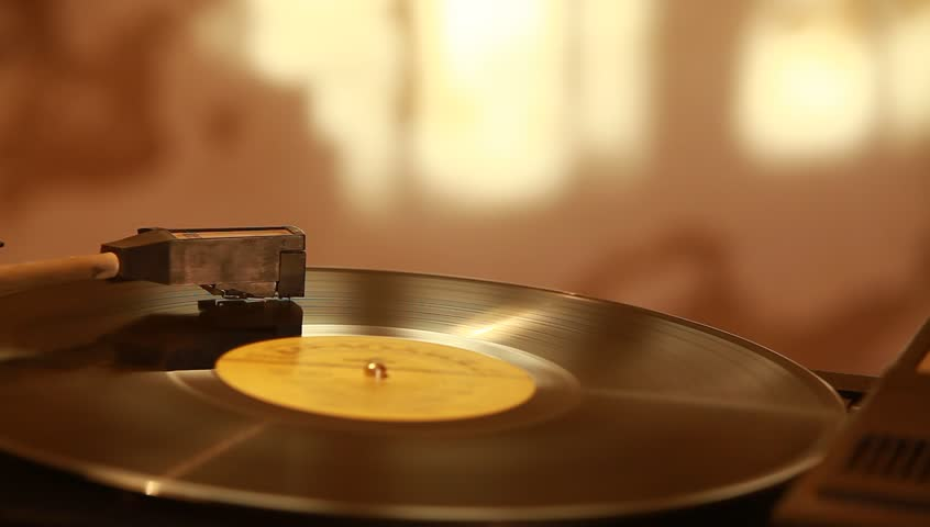 Gramophone record plaing on a warm background.