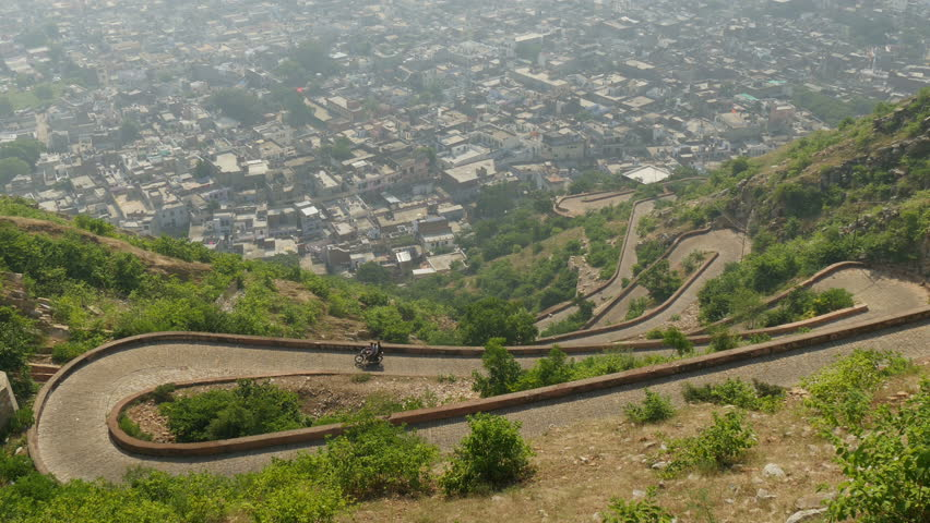 JAIPUR, INDIA - 21 OCTOBER 2014: A motorbike takes a winding road up from the city of Jaipur. - 4K stock video clip