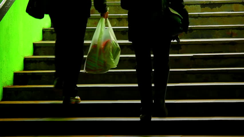 A couple on dark green staircase. Two adult people walk up the stars. Man holds a plastic bag from the store. Source: Canon 7D, graded.