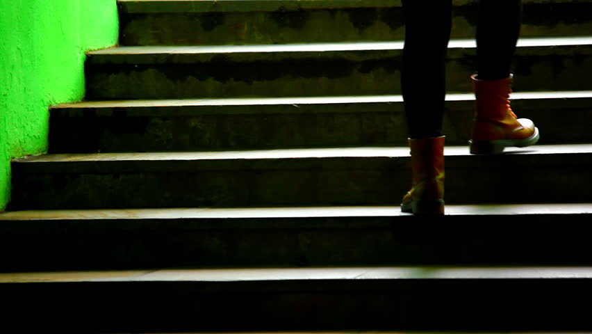 Woman on dark green staircase. Woman in red shoes walking up the stars. Source: Canon 7D, graded.