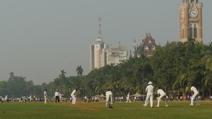 MUMBAI, INDIA - 2 NOVEMBER 2014: People play cricket in front of the Bombay University and a large Tata office.