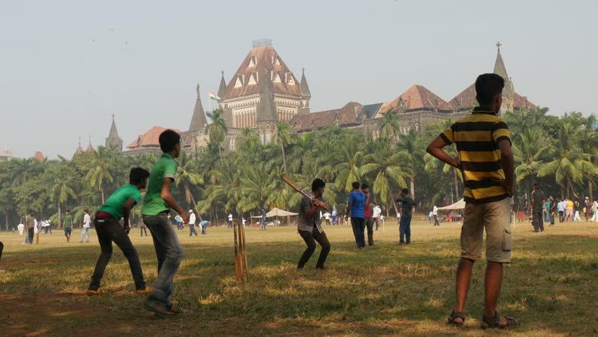 MUMBAI, INDIA - 2 NOVEMBER 2014: People play cricket in front of the Bombay University. - 4K stock footage clip