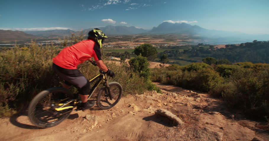 Extreme trail rider maneuvering his mountain biker over rough terrain on an off-road trail in slow motion
