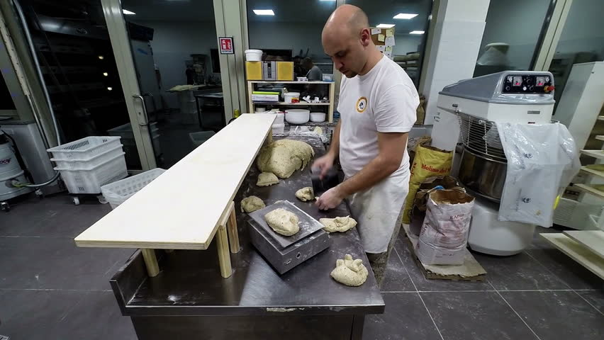 Baker working on bread dough using his hands. He is preparing piece of bread for last leavening - HD stock video clip