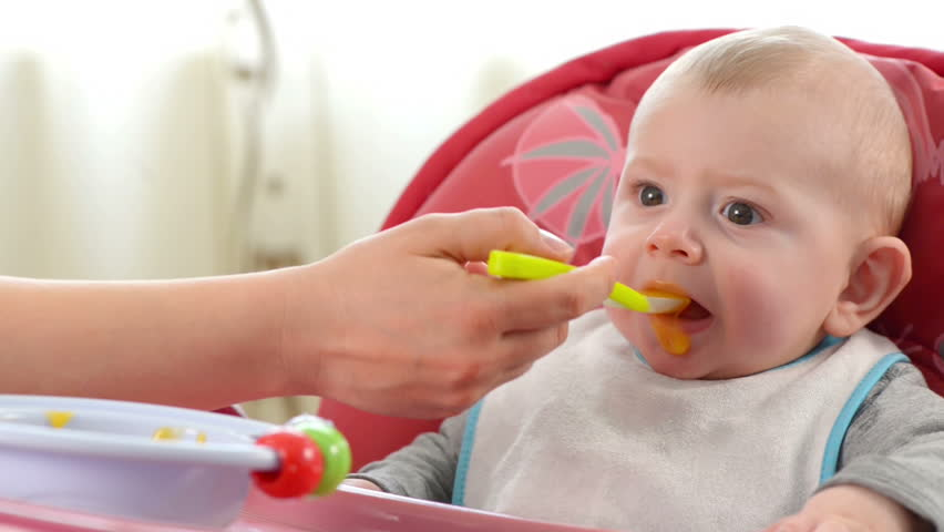 Baby boy eating in a high chair at home