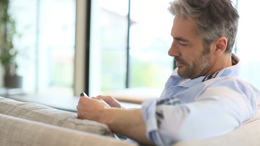 Attractive Young Man Relaxing At Home Alone Reading A
