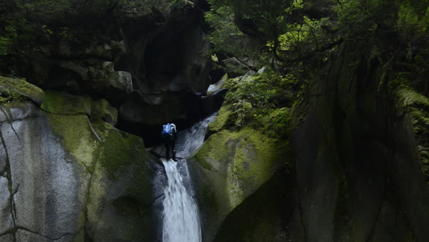A canyoneer abseils down a waterfall and slips