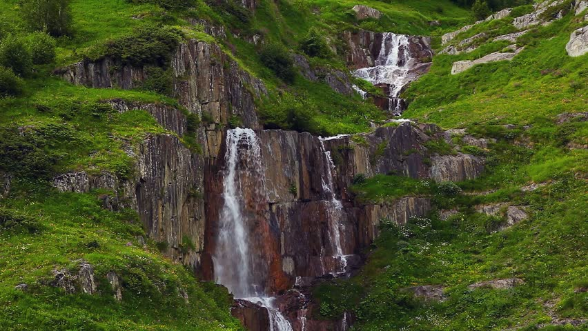 The picturesque waterfall at the foot of Mt. Shkhara. Upper Svaneti, Georgia, Europe. The main Caucasus ridge. Dramatic unusual scene. Beauty world. HD video (High Definition)