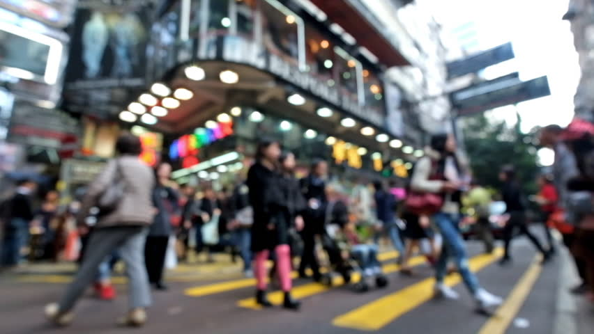 Abstract cityscape blurred background. Unrecognizable people walking on crosswalk in crowded city street with modern shopping malls Hong Kong. Blur effect | Shutterstock HD Video #9597404