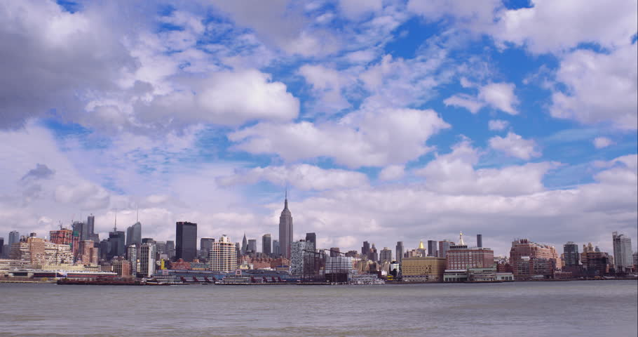 Time-lapse of clouds in a blue sky passing over the Midtown Manhattan skyline | Shutterstock HD Video #9616070