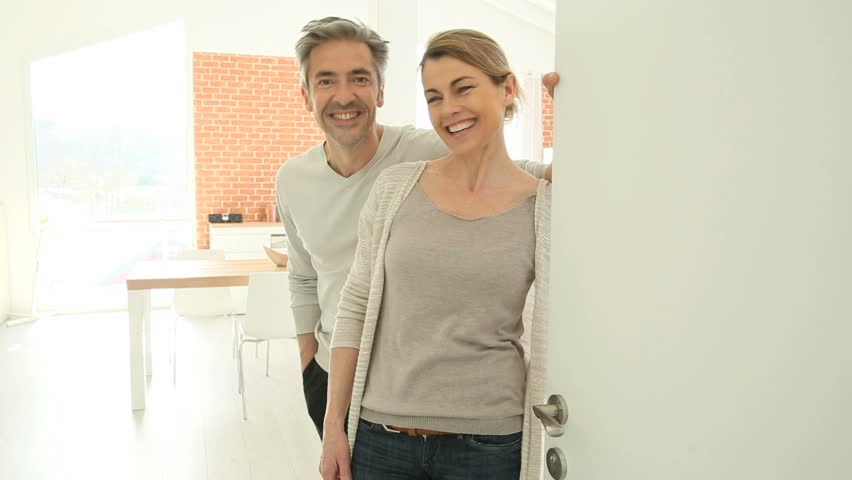 Couple opening house's front door to let people in