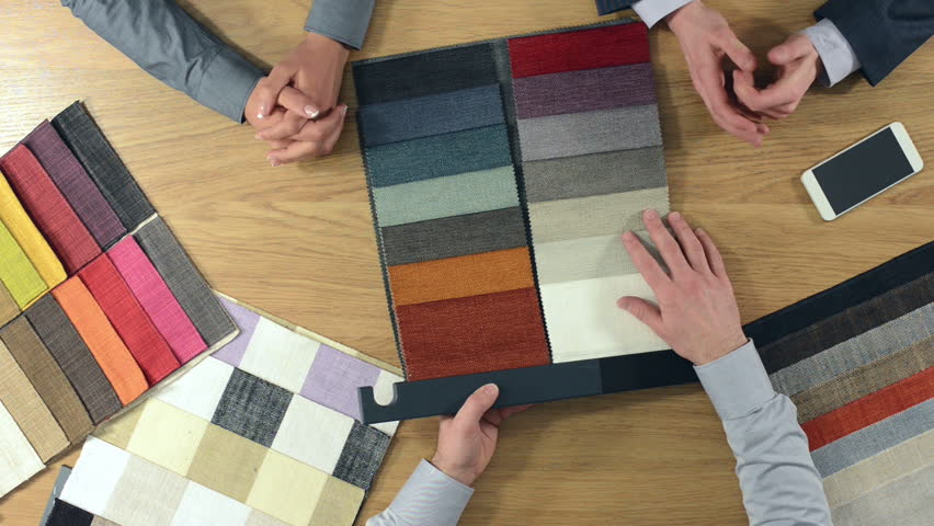 Home decorator showing fabric swatches to his customers and touching the textile's textures, hands top view