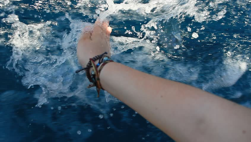 Hand holding the surface of water with ripples. Girl touching surface of water while relaxing on the deck of boat.