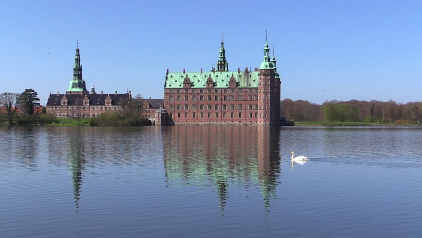 Swan swimming in front of Frederiksborg Castle in Hilleroed, Denmark, on a sunny spring day. The castle is built in Dutch Renaissance style and is located on three islands in the castle lake.  - HD stock footage clip