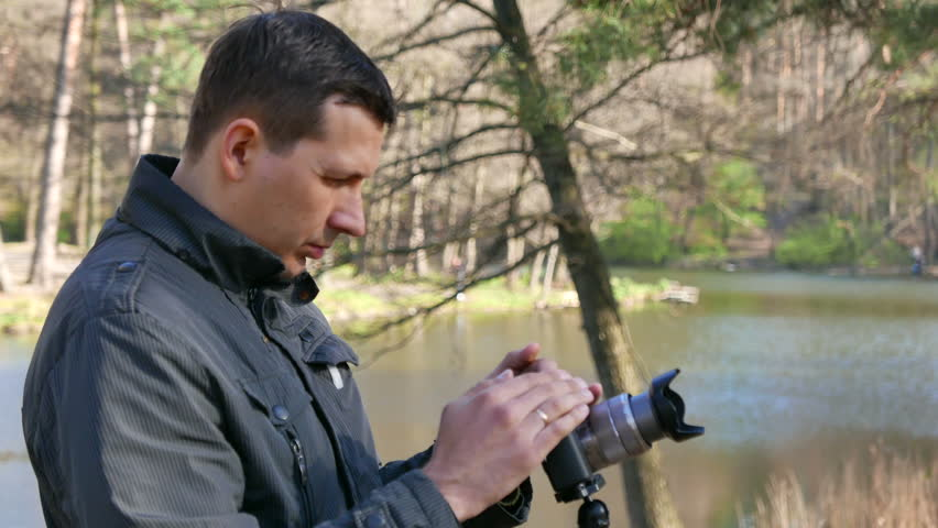 Man  photographer works with camera in wood,4K 3840x2160 - 4K stock video clip