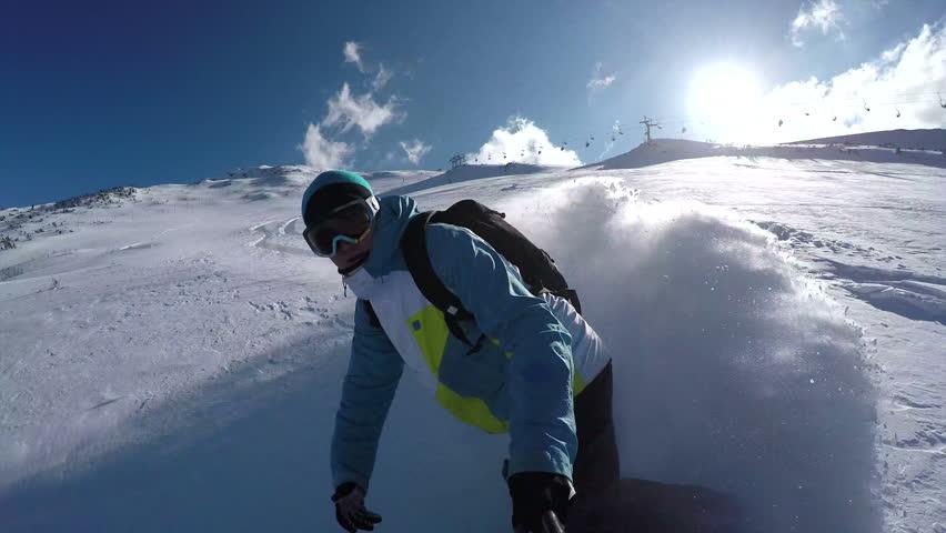 SELFIE: Snowboarder riding powder snow in mountain ski resort