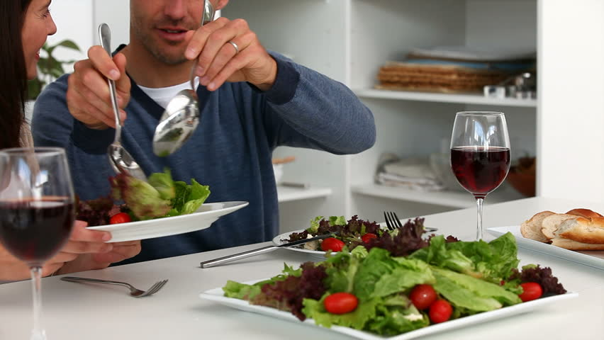 Man serving salad to his wife during lunch in the kitchen - HD stock video clip