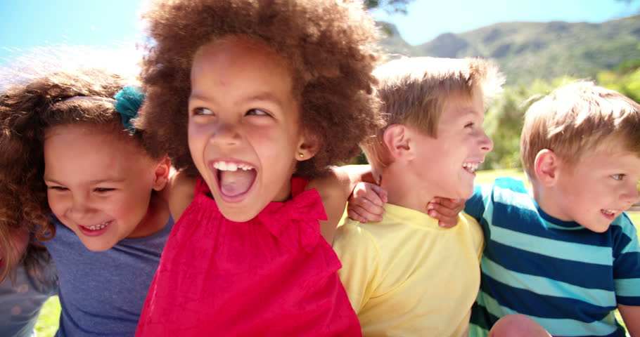 Happy mixed racial group of friendly children sitting in the sun laughing together, Panning in Slow Motion - 4K stock video clip