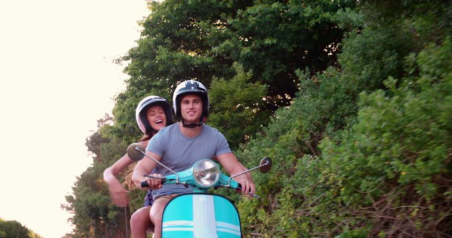 Happy couple feeling free while road tripping on their scooter in Slow Motion