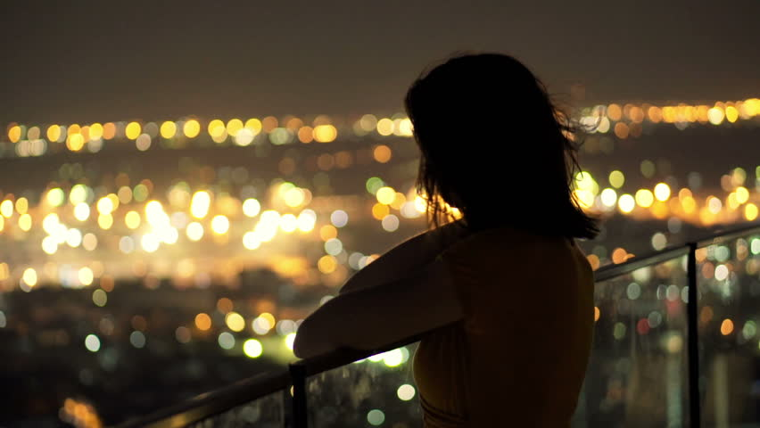 Young pensive woman looking at cityscape in the evening lights