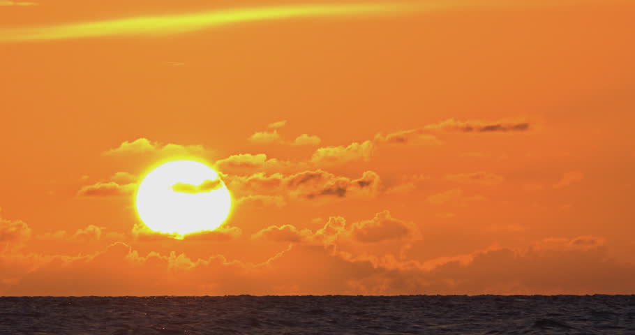 Amazing sunset in Santa Maria key beach, pov from inside the water, orange sky with some clouds where a large sphere of sun goes down the horizon in the water