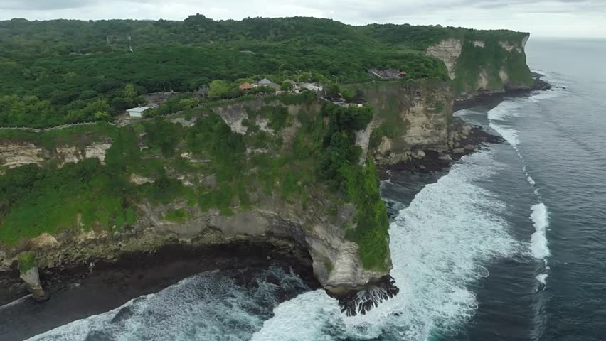 Pura Luhur Uluwatu, Aerial Shot travelling from high cliff towards the sea - HD stock footage clip