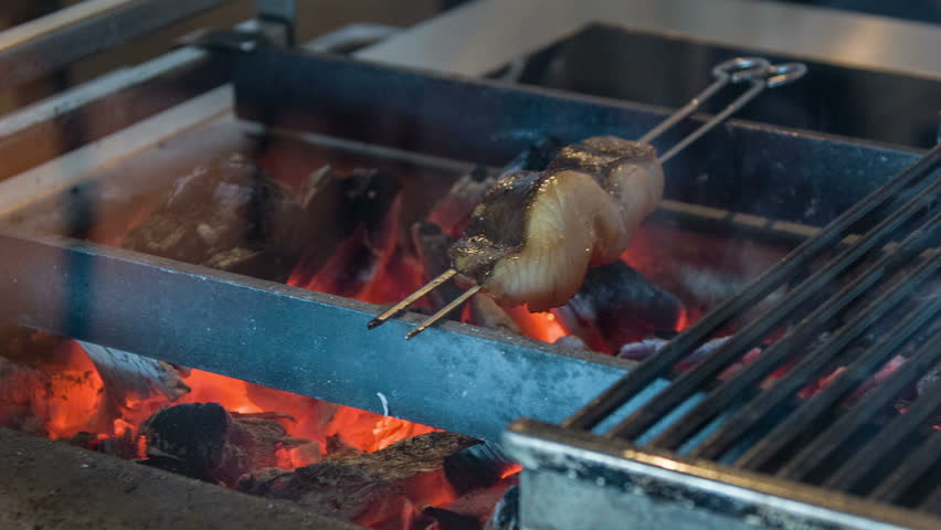 Do you want to taste. Horizontal dolly shot of appetizing T-bone steak lying on grill in some restaurant kitchen