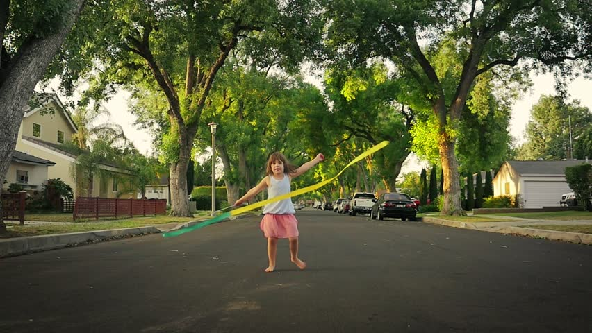 Happy cute girl dancing with ribbon on a beautiful suburban street with green trees in background. Slow motion.
