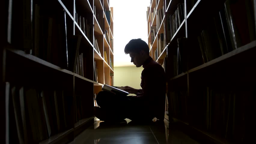 college student sitting on floor in library, reading book. Vertical shape, side view, full length, copy space