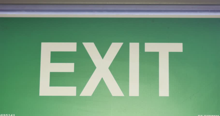 Close up shot of an exit sign, the shot goes out of focus and comes back in focus/The exit