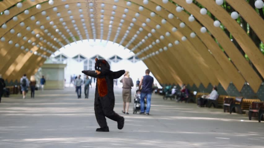 Actor dresses in bear suit runs and jumps on alley of park.