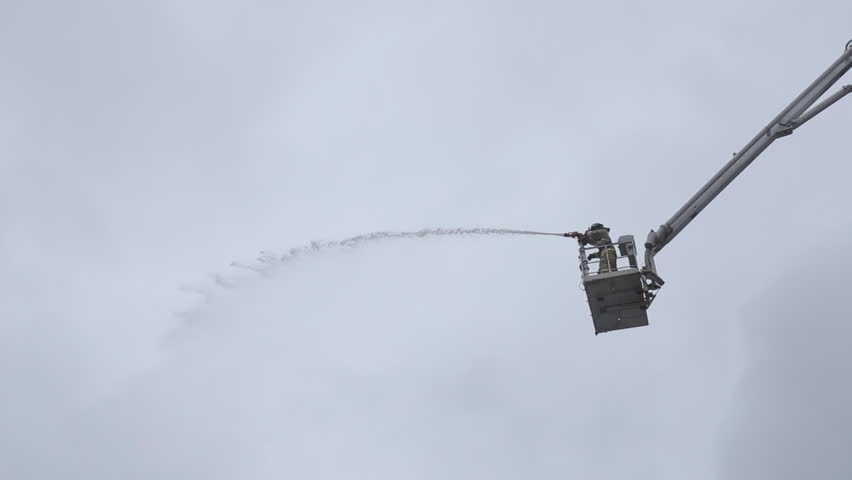 SEVASTOPOL,CRIMEA/RUSSIA-MARCH 26,2015: Firefighter in tall and long crane, Water jet splashing with high pressure on March 26, 2015 in Sevastopol, Russia | Shutterstock HD Video #9959978