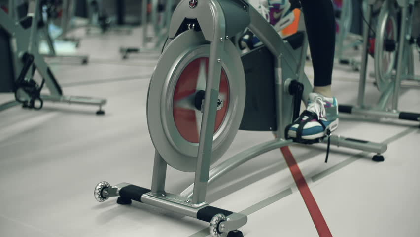 Tilt up the unrecognizable girl doing cardio on gym cycling machine