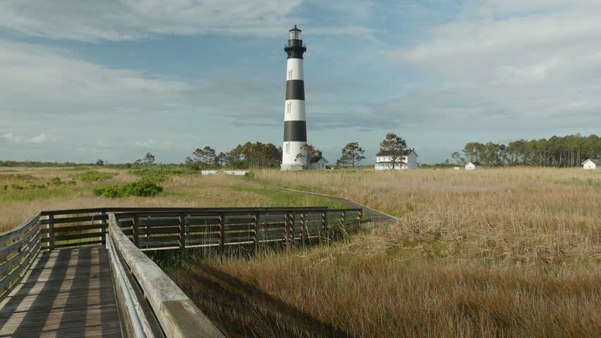 An early morning view of the Bodie Island lighthouse and boardwalk winding through blowing marsh grass under a partly cloudy sky in Cape Hatteras National Seashore in the Outer Banks of North Carolina - 4K stock footage clip
