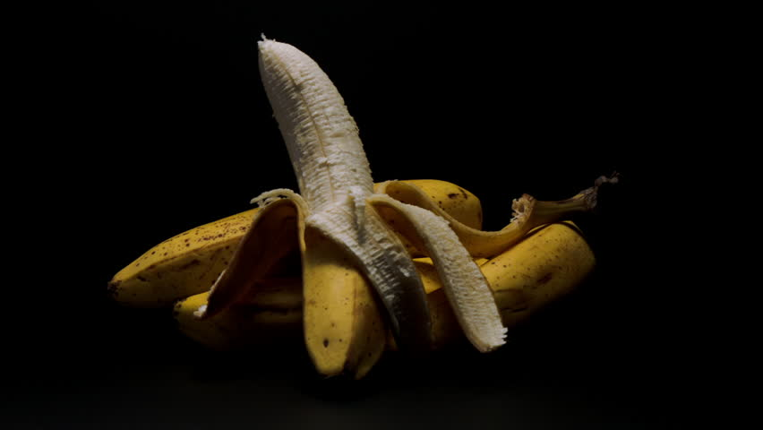 FOUR BANANAS, ONE IS HALF NAKED, ON A DRAMATIC, MATTE BLACK BACKGROUND. HIGH CONTRAST SHOT. - HD stock video clip