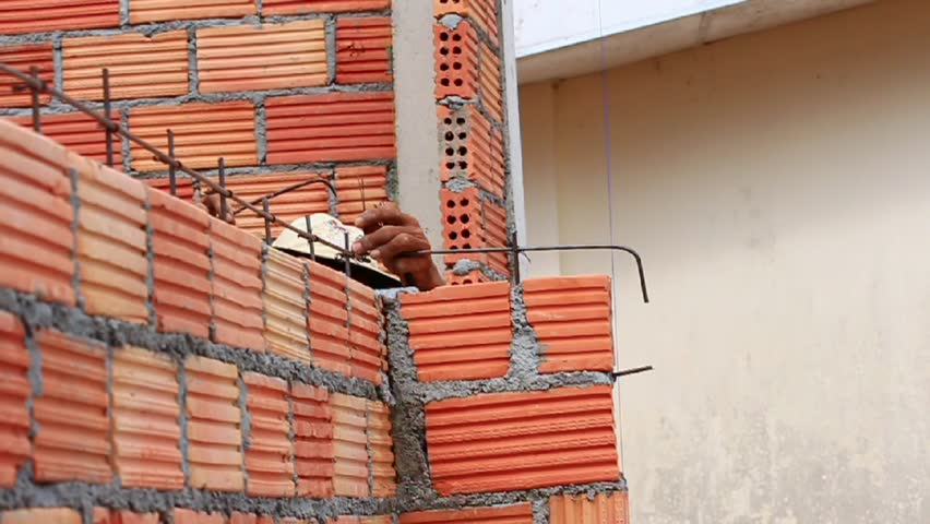 Construction Workers Laying Bricks Building Wall.